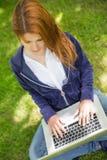 放松在公园的俏丽的红头发人使用膝上型计算机 免版税库存图片