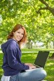 放松在公园的俏丽的红头发人使用膝上型计算机 库存照片
