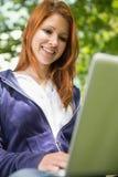 放松在公园的俏丽的红头发人使用膝上型计算机 免版税图库摄影