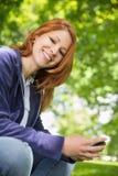 放松在公园的俏丽的红头发人送文本 库存图片