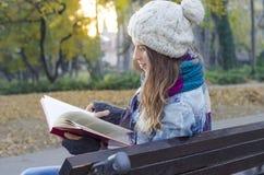 放松在公园的女孩,读书 免版税库存图片