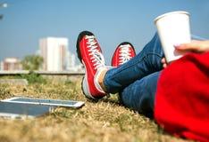 放松在公园的牛仔裤的女孩和红色夹克和鞋子 免版税库存图片