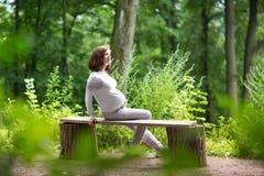 放松在公园的年轻人孕妇在活跃步行以后 免版税库存照片