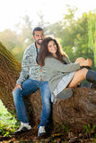 放松在公园的年轻和微笑的夫妇 免版税库存照片