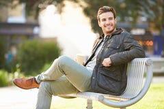 放松在公园长椅的人用外带的咖啡 免版税库存图片