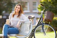 放松在公园长椅的妇女用外带的咖啡 免版税库存照片
