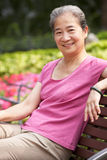 放松在公园长椅的高级中国妇女 免版税图库摄影