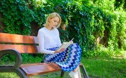 放松在公园阅读书的妇女白肤金发的作为断裂 作为爱好的读书文学 书是她的激情 敏锐的女孩  免版税库存照片