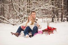 放松在冬天森林里的夫妇 库存图片