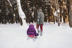 放松在冬天森林里的父亲和女儿 库存照片