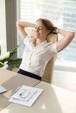 放松在办公室椅子的微笑的妇女,轻松在工作, vertica 库存照片