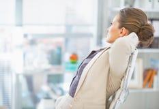 放松在办公室的女商人 图库摄影