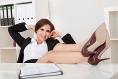 放松在办公室的愉快的女实业家 库存照片
