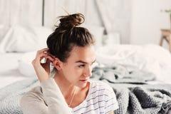 放松在卧室的美丽的年轻女性性感的妇女在懒惰周末早晨,佩带的偶然时尚 免版税库存图片