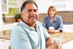 放松在厨房里的高级夫妇 免版税库存照片