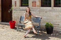 放松在古色古香的房子前面的长凳的女孩 免版税图库摄影