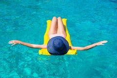 放松在可膨胀的床垫的妇女在清楚的海 免版税库存照片