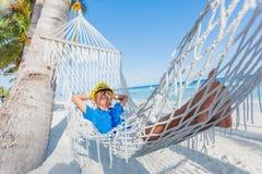 放松在吊床的一个热带海滩的小男孩 库存照片