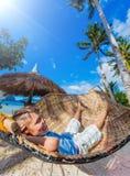 放松在吊床的一个热带海滩的小男孩 免版税库存图片