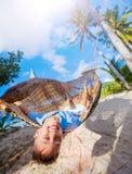 放松在吊床的一个热带海滩的小男孩 库存图片