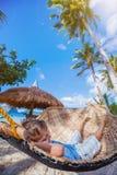 放松在吊床的一个热带海滩的小男孩 免版税库存照片