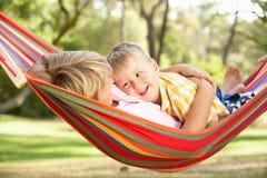 放松在吊床的二个男孩 库存图片