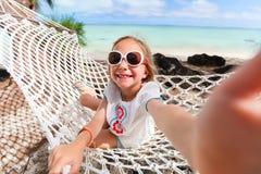 放松在吊床的可爱的小女孩 免版税库存图片