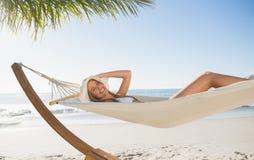 放松在吊床的妇女佩带的sunhat和比基尼泳装微笑对照相机 免版税图库摄影