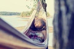 放松在吊床的妇女,在海旁边 库存图片