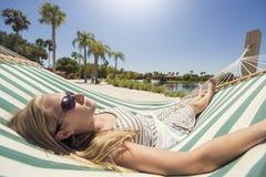 放松在吊床的妇女,当在度假时 免版税库存照片