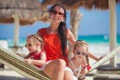 年轻放松在吊床的妈妈和小女儿 免版税库存图片
