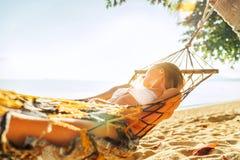 放松在吊床的年轻白肤金发的长发妇女取决于在棕榈树之间沙滩 库存照片