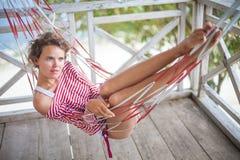 放松在吊床的海滩平房的照片年轻俏丽的女孩 微笑的妇女消费冷颤时间室外夏天 免版税图库摄影