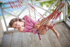 放松在吊床的海滩平房的照片年轻性感的女孩 微笑的妇女消费冷颤时间室外夏天 加勒比 库存图片