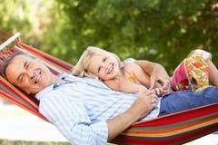 放松在吊床的祖父和孙女 免版税库存图片