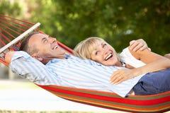 放松在吊床的高级夫妇 免版税库存图片