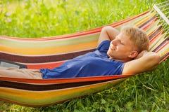 放松在吊床的年轻人 免版税库存照片