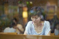 放松在咖啡店的中国妇女 库存照片