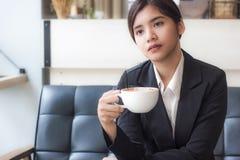 放松在咖啡店的亚裔女商人用热的咖啡 库存图片
