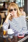 放松在咖啡店的微笑的妇女 免版税库存照片
