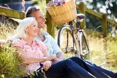 放松在国家周期乘驾的中世纪夫妇 免版税库存图片