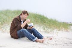 放松在圣皮特圣徒・彼得海滩的沙丘的年轻愉快的人  免版税库存图片
