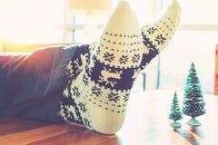 放松在圣诞节主题的袜子的人 免版税库存照片