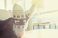 放松在圣诞节主题的袜子的人 免版税库存图片