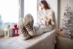 放松在圣诞节装饰的窗口基石的年轻美丽的妇女 图库摄影
