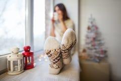 放松在圣诞节装饰的窗口基石的年轻美丽的妇女 免版税库存图片