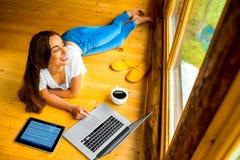 放松在地板上的妇女在木房子里 图库摄影