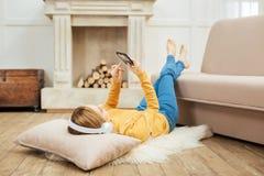 放松在地板上的白肤金发的少妇 免版税库存照片