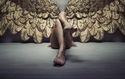 放松在地板上的金子天使的图片 库存照片