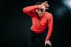放松在坚硬锻炼以后的可爱的严肃的人运动员在健身房,在头上把他的手放 穿红色运动服的运动的人 免版税库存照片